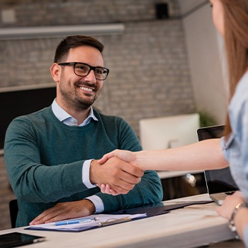 Man shaking hands with woman in dental office