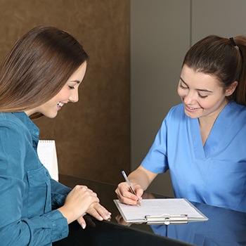 Woman looking at dental insurance forms with dentistry team member