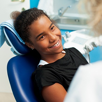 Young girl in dental chair for dental checkup smiling at dentist