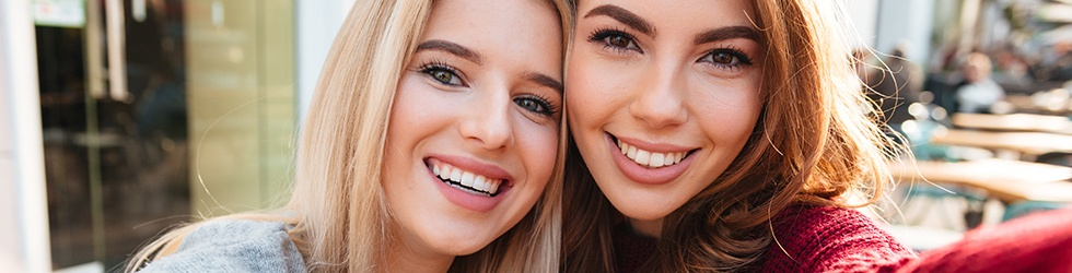 Two women showing off beautiful smiles after cosmetic dentistry