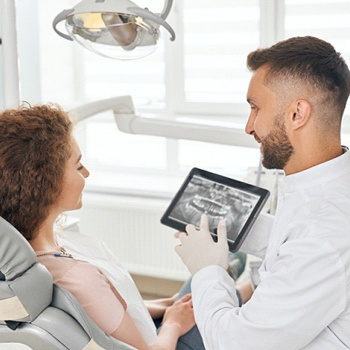 A dentist showing a female patient who is sitting in the dentist's chair a digital image of her oral cavity and where the dental crown will be placed