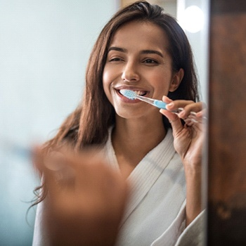 A dark-haired young woman using a manual toothbrush to brush her teeth while standing in front of the mirror