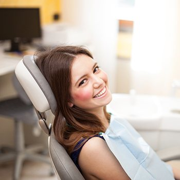 A young woman smiling in a dental chair.
