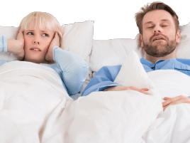Woman covering her ears in bed next to snoring man