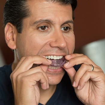 Man placing nightguard for bruxism