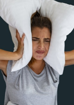 Woman covering ears because of snoring