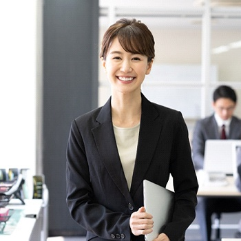 persons smiling and standing in an office