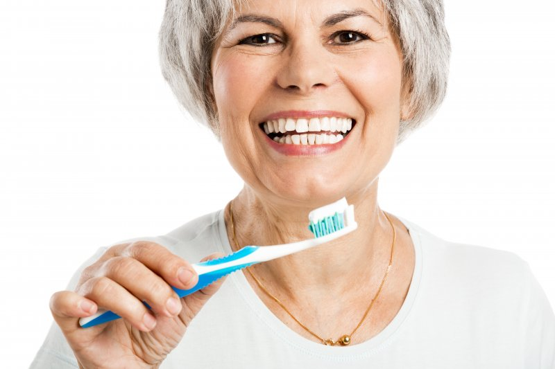 Woman about to practice dental implant surgery aftercare by brushing
