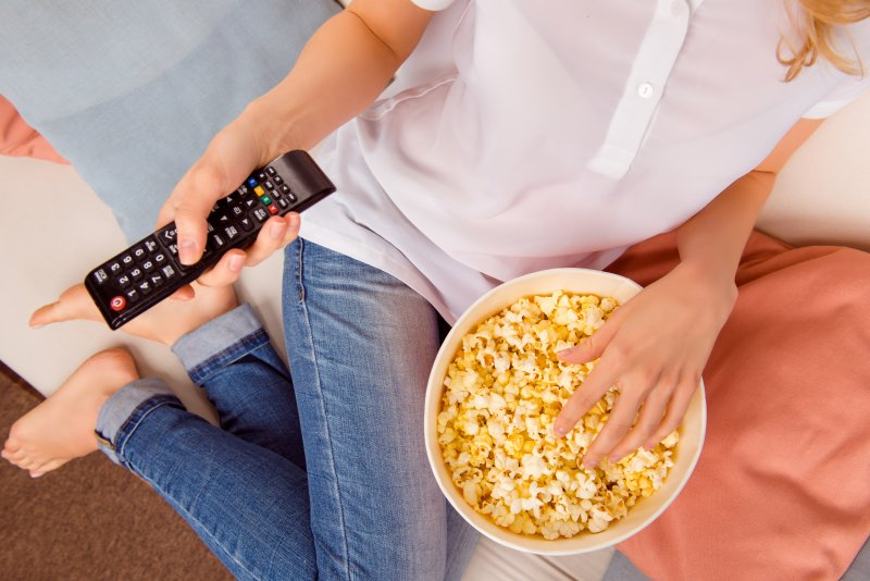 young woman sitting on couch eating popcorn