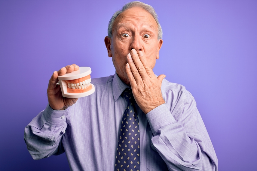 older man with hand over mouth holding dentures